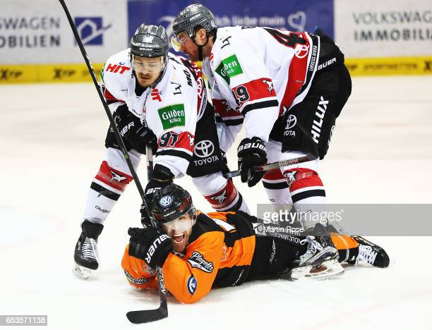 Nick Johnson of the Grizzlys Wolfsburg is challenged by Moritz Mueller and Alexandre Bolduc of Koelner Haie during the DEL Playoffs Quarter Final...