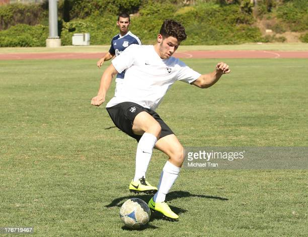 Nick Jonas and Joe Jonas play soccer at The Jonas Brothers host a charity soccer match held at StubHub Center - track and field on August 17, 2013 in...