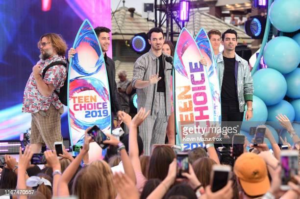 Nick Jonas, Kevin Jonas, and Joe Jonas of Jonas Brothers accept the Teen Choice Decade Award from Jack Black onstage during FOX's Teen Choice Awards...