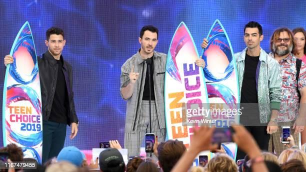 Nick Jonas Kevin Jonas and Joe Jonas of Jonas Brothers accept the Teen Choice Decade Award from Jack Black onstage during attends FOX's Teen Choice...
