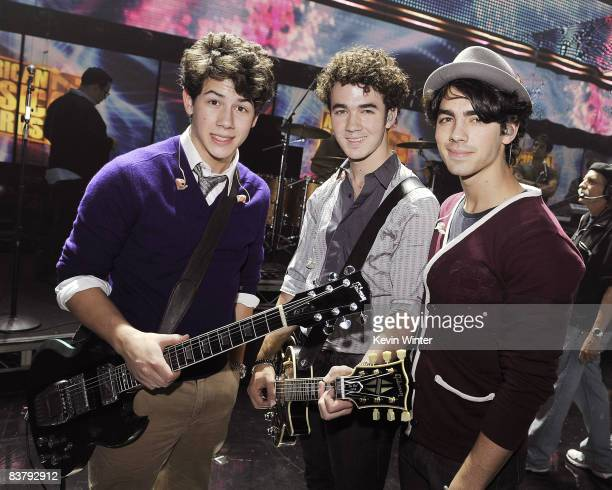 Nick Jonas Kevin Jonas and Joe Jonas of the Jonas Brothers pose during rehearsals for the 2008 American Music Awards at the Nokia Theatre on November...