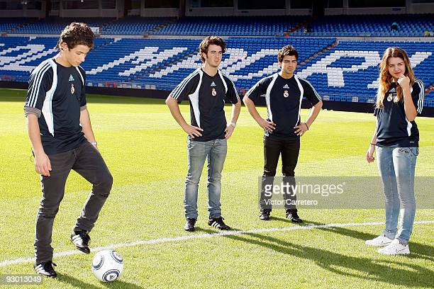 Nick Jonas Kevin Jonas Joe Jonas and Andrea Guasch of the Disney Channel Spain stand on the pitch during a visit of the Jonas Brothers as guests of...