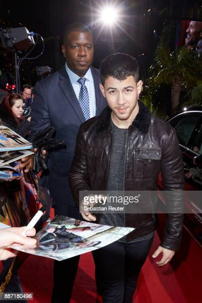 Nick Jonas signs autographs as he arrives for the German premiere of 'Jumanji Willkommen im Dschungel' at Sony Centre on December 6 2017 in Berlin...