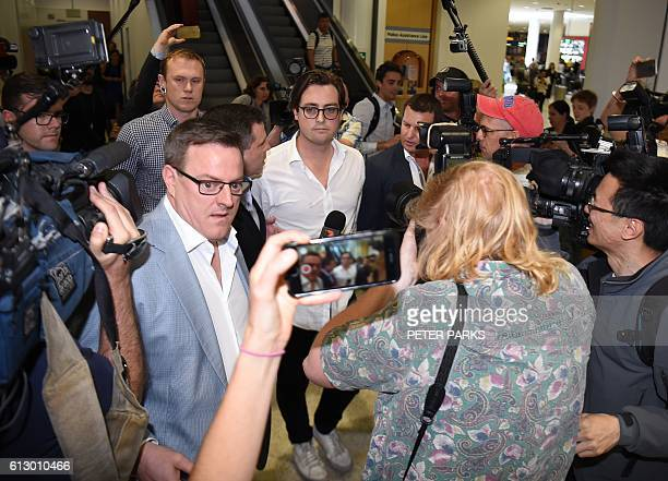 Nick Kelly from the group of nine dubbed the 'Budgie Nine' walks through a media scrum after arriving at Sydney Airport on October 7 2016 Nine...