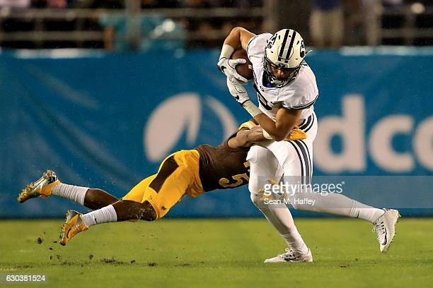 Nick Kurtz of the Brigham Young Cougars eludes the tackle of Rico Gafford of the Wyoming Cowboys during the first half of the Poinsettia Bowl at...
