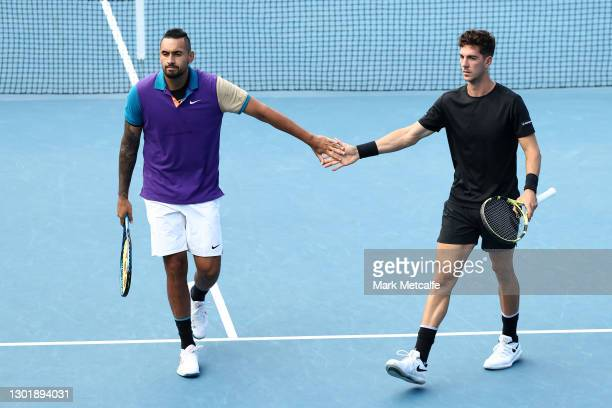 Nick Kyrgios and Thanasi Kokkinakis of Australia high five in their Men's Doubles second round match against Lloyd Harris of South Africa and Julian...