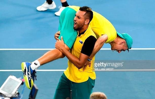 TOPSHOT Nick Kyrgios of Australia carries teammate Alex de Minaur after winning their men's doubles match against Jamie Murray and Joe Salisbury of...