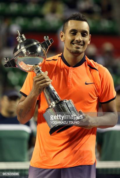 Nick Kyrgios of Australia holds the trophy of the Rakuten Japan Open tennis championships in Tokyo on October 9 2016 Kyrgios defeated David Goffin of...