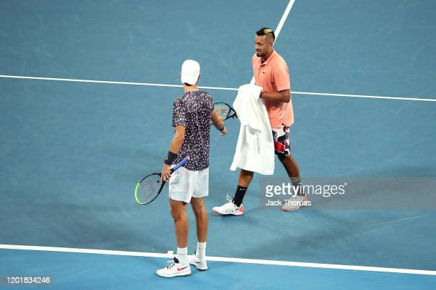 Nick Kyrgios of Australia walks around to the other side of the court to give Karen Khachanov of Russia a towel so he can wipe the floor during their...
