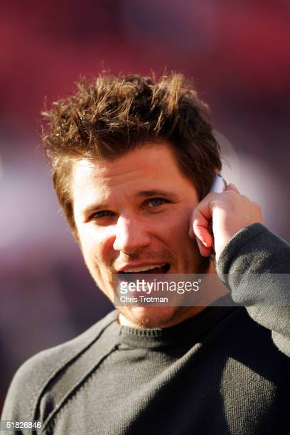 Nick Lachey talks on the phone during pregame before the New York Jets played the Houston Texans at Giants Stadium on December 5 2004 in East...