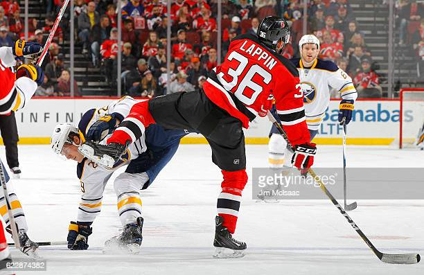 Nick Lappin of the New Jersey Devils collides with Jake McCabe of the Buffalo Sabres during the first period at the Prudential Center on November 12...