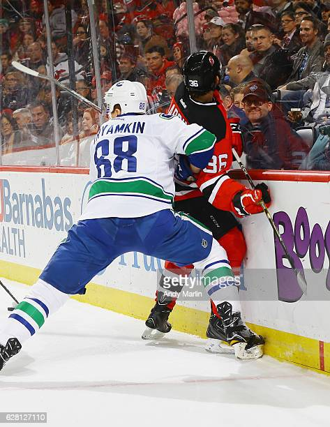 Nick Lappin of the New Jersey Devils is checked into the boards by Nikita Tryamkin of the Vancouver Canucks during the game at Prudential Center on...
