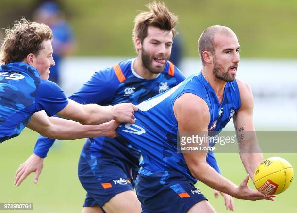 Kangaroos head coach Brad Scott listens to Shaun Higgins of the Kangaroos during a North Melbourne Kangaroos AFL training session at Arden Street on...