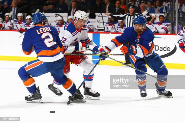 Nick Leddy and Dennis Seidenberg of the New York Islanders seperate Filip Chytil of the New York Rangers from the puck during the second period at...
