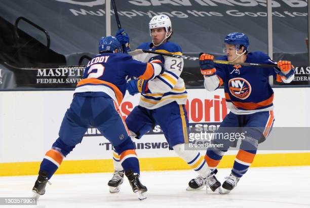 Nick Leddy and Mathew Barzal of the New York Islanders slow up Dylan Cozens of the Buffalo Sabres during the first period at the Nassau Coliseum on...