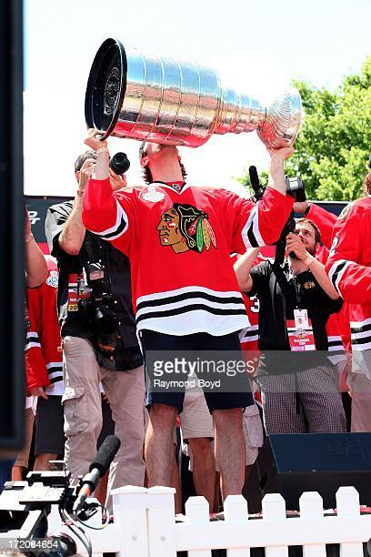 Nick Leddy defenseman for the Chicago Blackhawks raises and kisses the Stanley Cup Trophy during the Chicago Blackhawks' 2013 Stanley Cup...