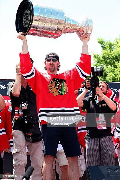 Nick Leddy, defenseman for the Chicago Blackhawks, raises the Stanley Cup Trophy during the Chicago Blackhawks' 2013 Stanley Cup Championship rally...