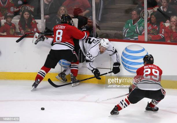 Nick Leddy of the Chicago Blackhawks checks Trevor Lewis of the Los Angeles Kings near the corner boards as Bryan Bickell of the Chicago Blackhawks...
