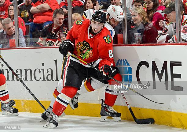 Nick Leddy of the Chicago Blackhawks looks across the ice as Akim Aliu of the Calgary Flames attempts to grab the puck from the boards during the NHL...
