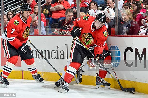Nick Leddy of the Chicago Blackhawks pushes into Akim Aliu of the Calgary Flames as Brent Seabrook of the Blackhawks follows behind during the NHL...