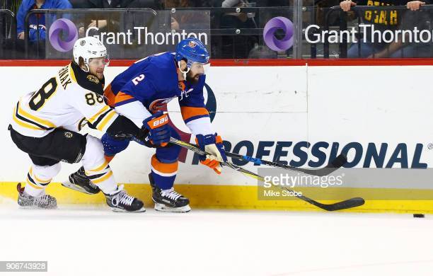 Nick Leddy of the New York Islanders and David Pastrnak of the Boston Bruins chase down a loose puck during the first period at Barclays Center on...