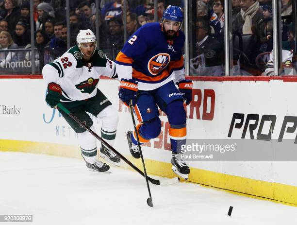Nick Leddy of the New York Islanders and Nino Niederreiter of the Minnesota Wild chase down a loose puck during the second period at Barclays Center...