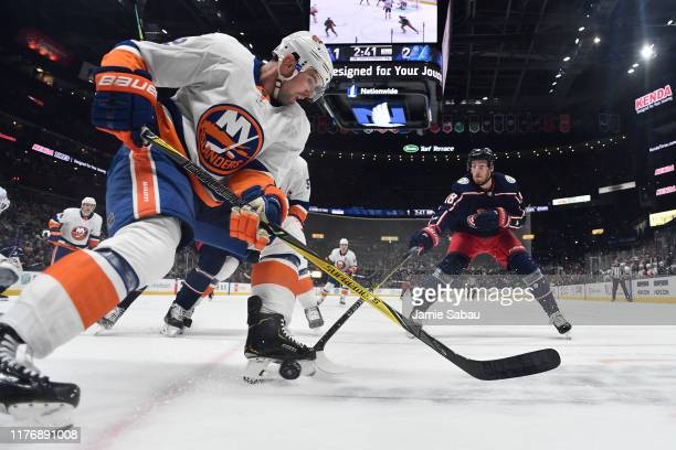 Nick Leddy of the New York Islanders battles for a loose puck with PierreLuc Dubois of the Columbus Blue Jackets during the first period of a game on...