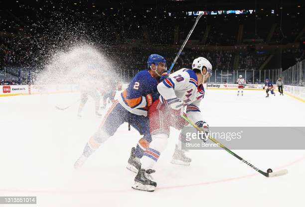 Nick Leddy of the New York Islanders checks Chris Kreider of the New York Rangers during the first period at the Nassau Coliseum on April 20, 2021 in...