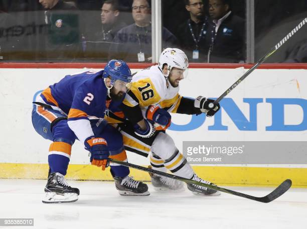 Nick Leddy of the New York Islanders holds on to Josh Jooris of the Pittsburgh Penguins during the first period at the Barclays Center on March 20...