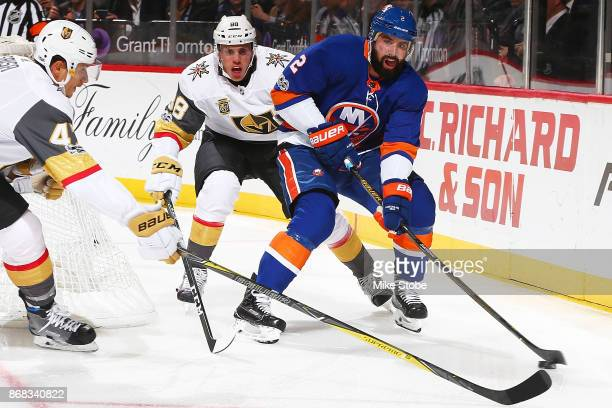 Nick Leddy of the New York Islanders looks to make a pass amid pressure from Nate Schmidt of the Vegas Golden Knights at Barclays Center on October...