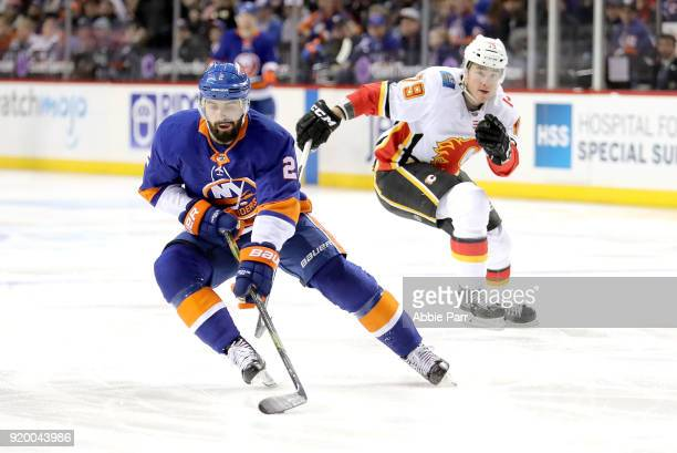 Nick Leddy of the New York Islanders skates with the puck against Micheal Ferland of the Calgary Flames in the first period during their game at...
