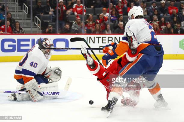 Nick Leddy of the New York Islanders takes Dylan Larkin of the Detroit Red Wings off his skates to prevent a shot on Semyon Varlamov during the...