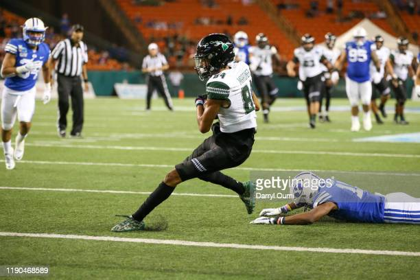 Nick Mardner of the Hawaii Rainbow Warriors manages to stay a step ahead of Isaiah Herron of the BYU Cougars after making a catch to go into the end...