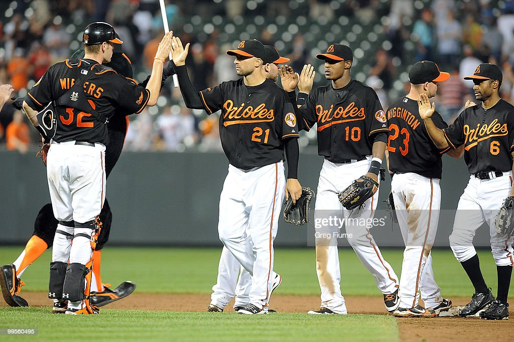 Nick Markakis #21, Adam Jones #10 and Corey Patterson #6 of the Baltimore Orioles celebrate with teammates after a 8-1 victory over the Cleveland Indians at Camden Yards on May 14, 2010 in Baltimore, Maryland.