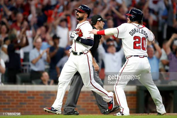 Nick Markakis and Josh Donaldson of the Atlanta Braves come in to score runs on an error against the St. Louis Cardinals during the sixth inning in...