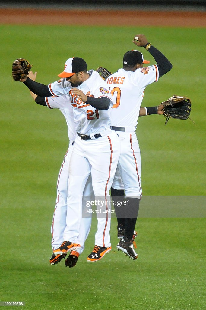 Nick Markakis #21, Dave Lough #9 and Adam Jones #10 of the Baltimore Orioles celebrate a win after a baseball game against the Boston Red Sox on June 11, 2014 at Oriole Park at Camden Yards in Baltimore, Maryland. The Orioles won 6-0.