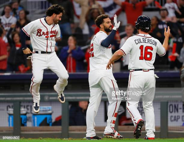 Nick Markakis of the Atlanta Braves celebrates with Dansby Swanson and Charlie Culberson after hitting a threerun homer in the ninth inning for a 85...