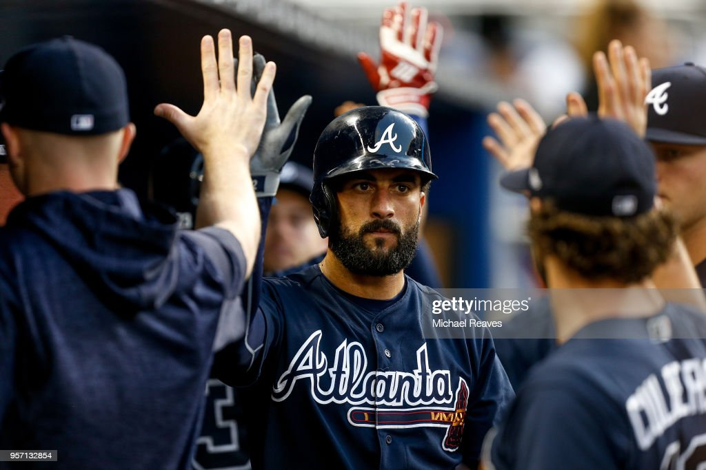 Nick Markakis #22 of the Atlanta Braves celebrates with teammates after scoring a run in the second inning against the Miami Marlins at Marlins Park on May 10, 2018 in Miami, Florida.
