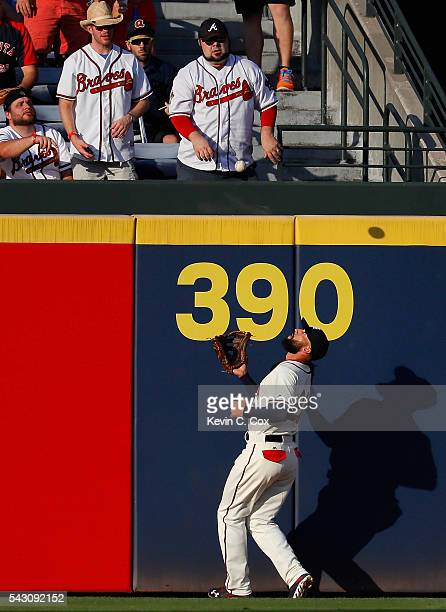 Nick Markakis of the Atlanta Braves chases down and catches a deep fly ball hit by Neil Walker of the New York Mets to end the first inning at Turner...