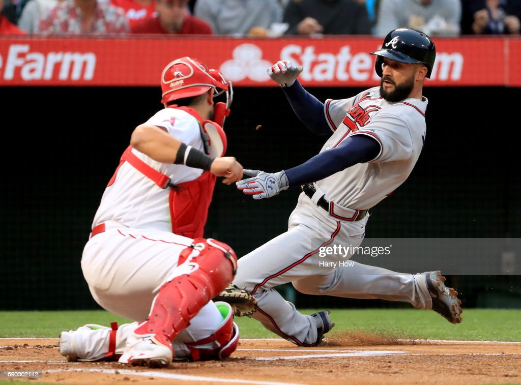 Nick Markakis #22 of the Atlanta Braves is caught trying to score as he is tagged out by Juan Graterol #59 of the Los Angeles Angels during the first inning at Angel Stadium of Anaheim on May 30, 2017 in Anaheim, California.
