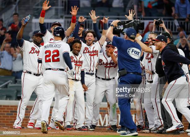 Nick Markakis of the Atlanta Braves is congratulated as he crosses homeplate after hitting a threerun homer in the ninth inning for a 85 win over the...