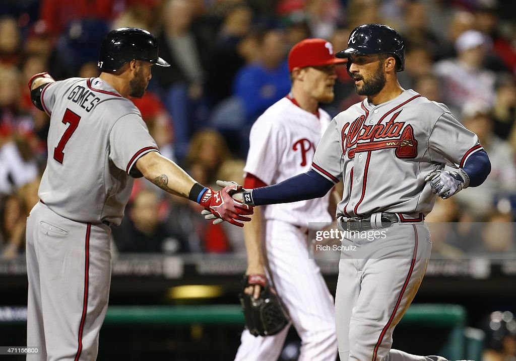 Nick Markakis #22 of the Atlanta Braves is congratulated by teammate Jonny Gomes #7 after scoring on a single by A.J. Pierzynski #15 during the eighth inning of a game at Citizens Bank Park on April 24, 2015 in Philadelphia, Pennsylvania.