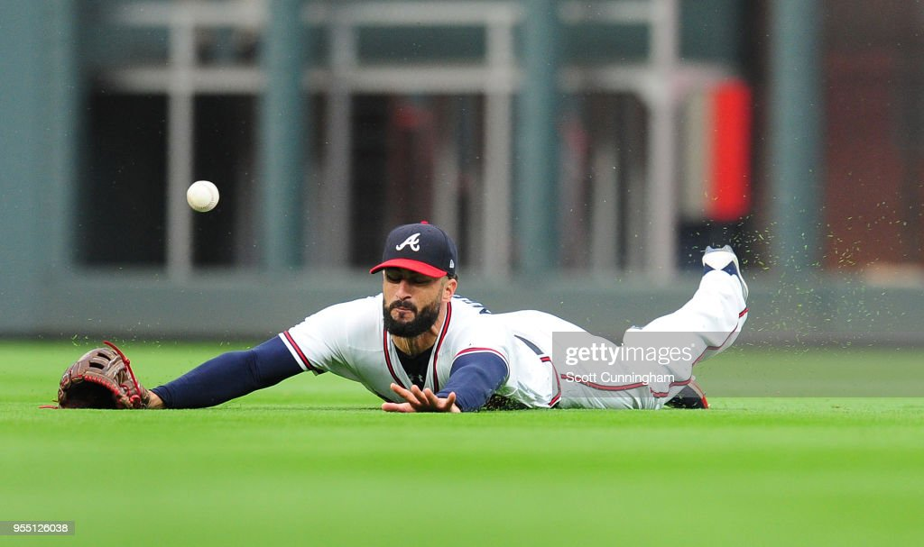 Nick Markakis #22 of the Atlanta Braves is unable to make a third inning diving catch against the San Francisco Giants at SunTrust Park on May 5, 2018 in Atlanta, Georgia.