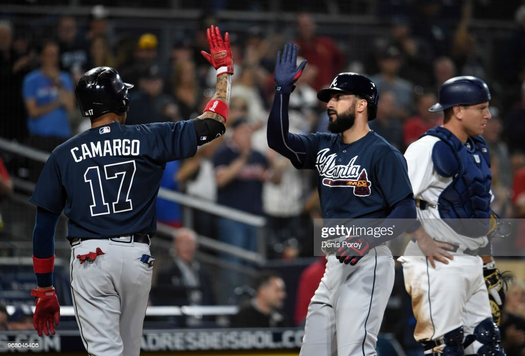 Nick Markakis #22 of the Atlanta Braves, right, is congratulated by Johan Camargo #17 after hitting a three-run home run during the seventh inning of a baseball game against the San Diego Padres at PETCO Park on June 5, 2018 in San Diego, California.