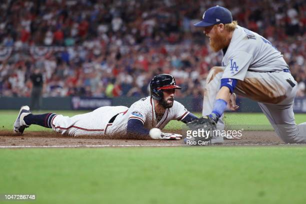 Nick Markakis of the Atlanta Braves slides safely into third base in the second inning as Justin Turner of the Los Angeles Dodgers waits for the...