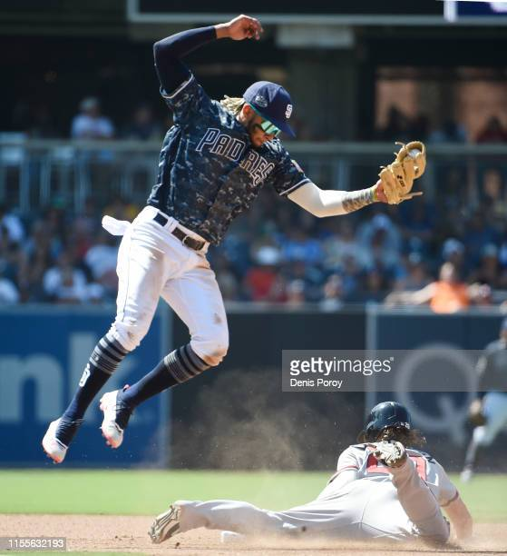 Nick Markakis of the Atlanta Braves steals second base as Fernando Tatis Jr #23 of the San Diego Padres jumps for a high throw during the eighth...