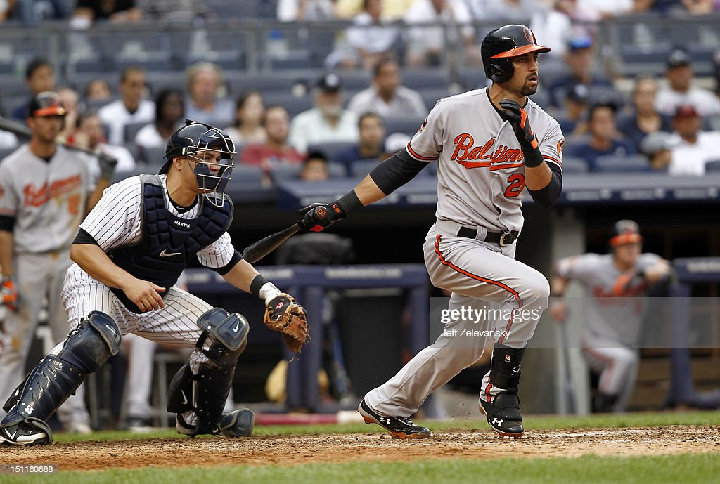 Nick Markakis #21 of the Baltimore Orioles hits a 2-RBI single in front of Russell Martin #55 of the New York Yankees at Yankee Stadium on September 2, 2012 in the Bronx borough of New York City.