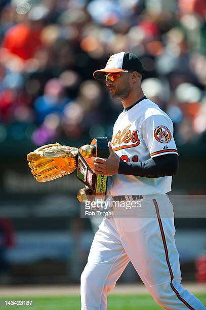 Nick Markakis of the Baltimore Orioles holds up his Golden Glove Trophy before the game against the Minnesota Twins at Oriole Park at Camden Yards on...