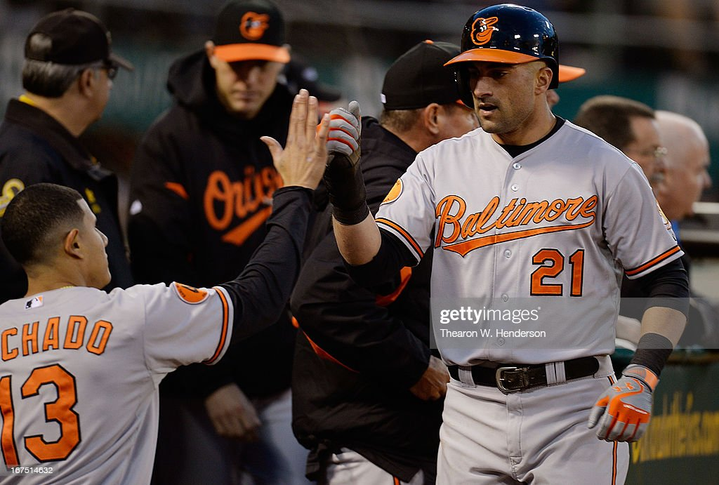 Nick Markakis #21 of the Baltimore Orioles is congratulated by Manny Machado #13 after Markakis scored from first base on an Adam Jones double against the Oakland Athletics in the third inning at O.co Coliseum on April 25, 2013 in Oakland, California.
