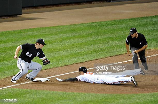 Nick Markakis of the Baltimore Orioles is tagged out trying to steal third base by Brent Morel of the Chicago White Sox at Oriole Park at Camden...